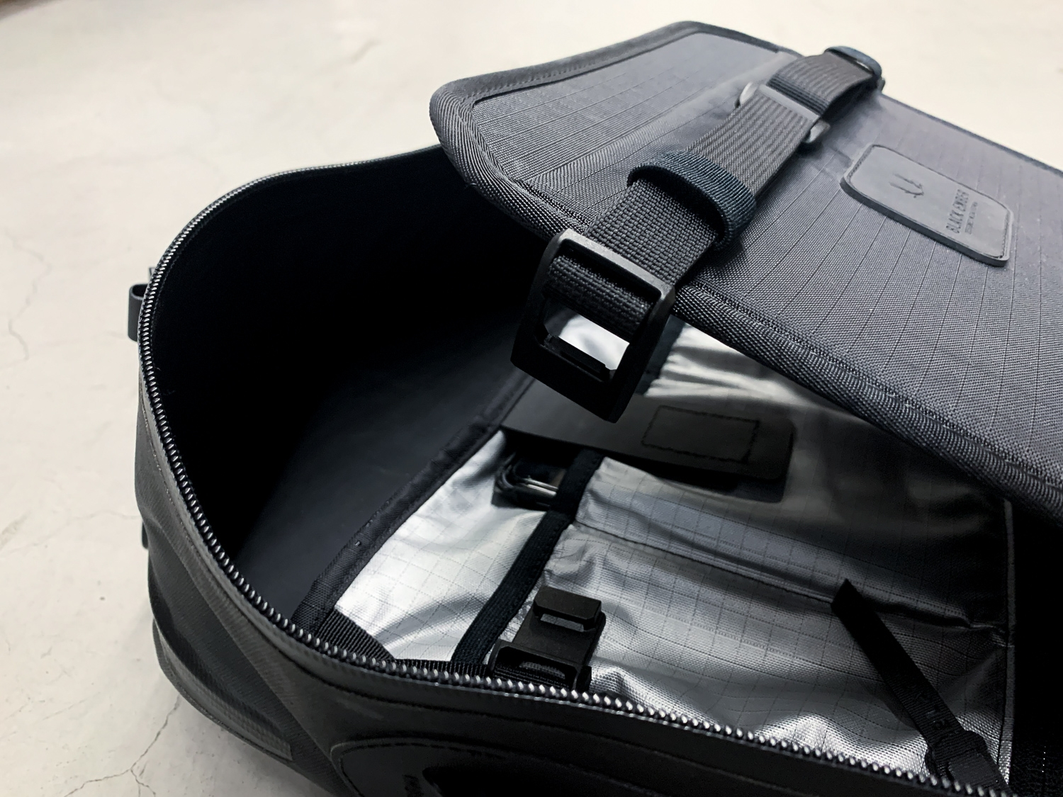 The black minimalist backpack comes from Black Ember with a compression divider to keep things flat and organized.