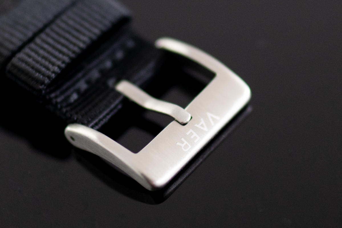 Debossed logo on the nylon strap buckle of the Vaer C5 Watch.