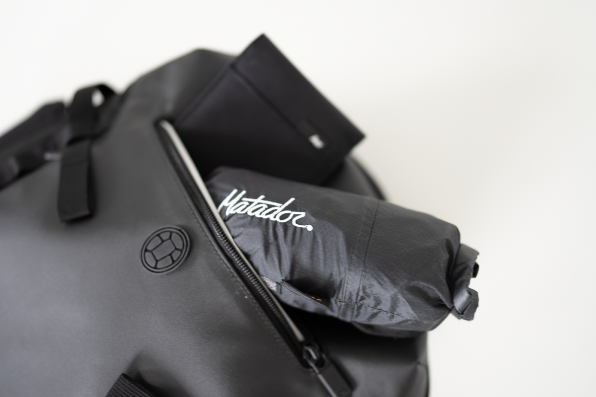 With the Aer Travel Wallet and the Matador Freerain24 2.0 Packable Backpack. Both fits into the quick access pocket of the Tortuga Prelude Travel Backpack.