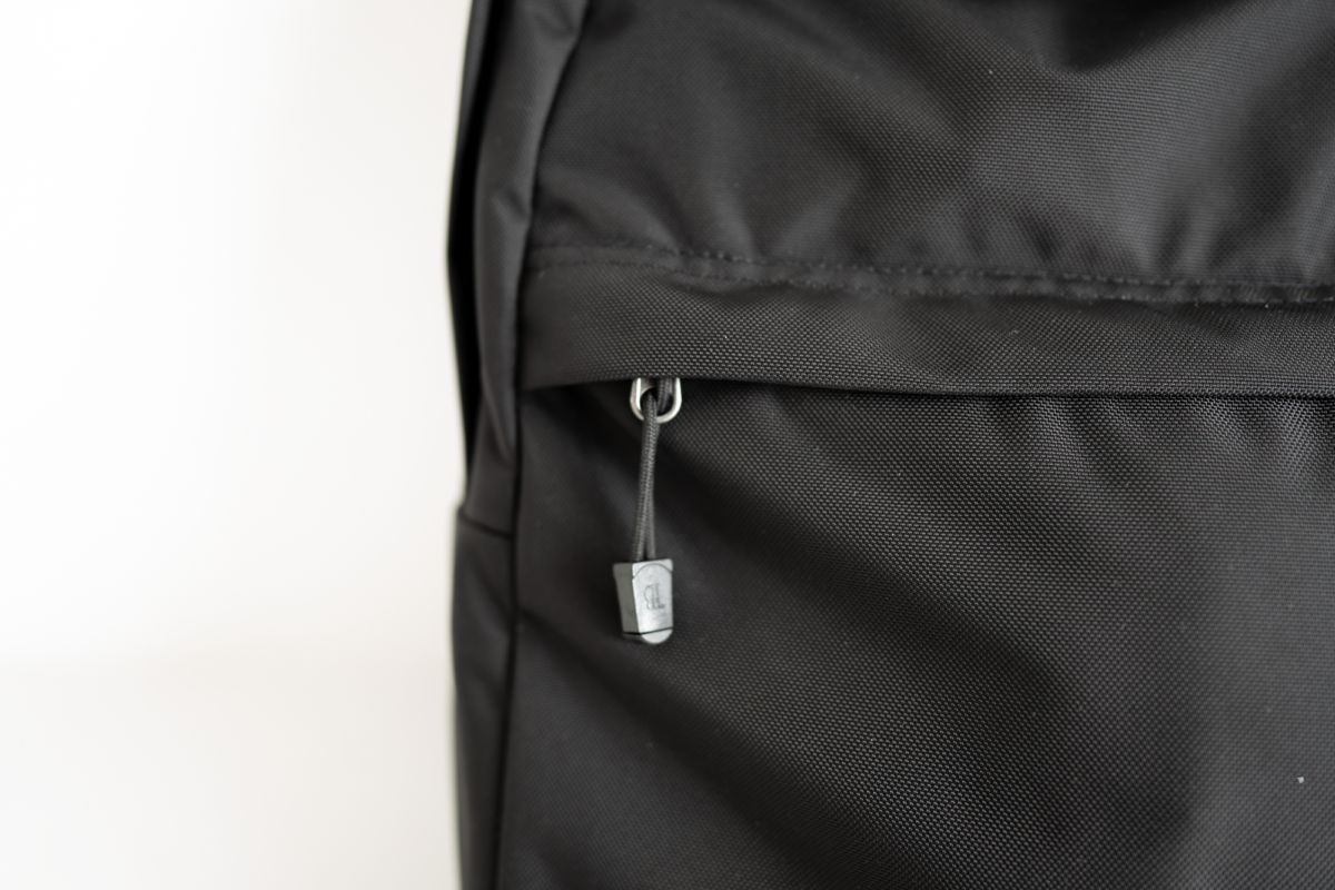 The zipper pull tab peeks out of the hidden pocket on the TOM BIHN Paragon Backpack.